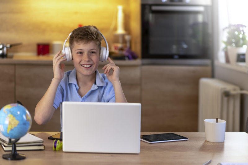 Photo of smiling student sitting at the kitchen table, online learning with laptop and smartphone during the day at home, looking at camera with smile. Teenage boy with headphones using laptop at table in room. 11 years old boy sitting behind a laptop doing online school while smiling.