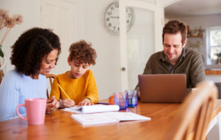 Father Works On Laptop As Mother Helps Gifted & Talented Child With Home work On Kitchen Table